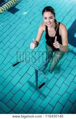 Fit woman cycling with thumbs up in swimming pool