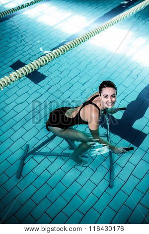 Fit smiling woman cycling on a swimming bike in swimming pool