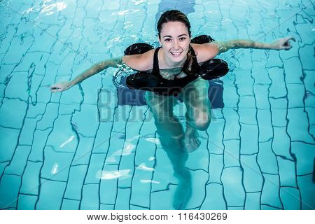 Fit smiling woman doing aqua aerobics in swimming pool