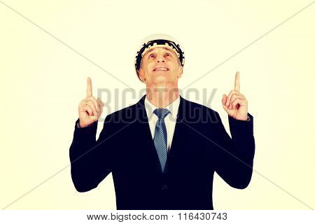 Smiling businessman with hard hat pointing up