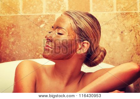 Relaxed woman sitting in a bath with closed eyes