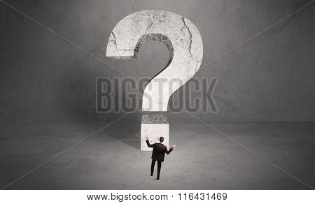 A small elegant business person in suit standing with his back in front of a huge question mark in open space concept