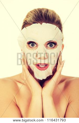 Young surprised woman with facial mask