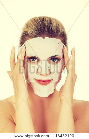Young happy woman with facial mask.