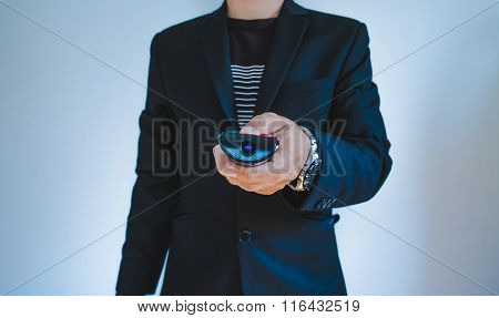 Businessman in casual suit push remote control, selective focus