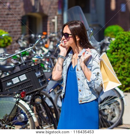 Young caucasian woman talking by cell phone in european city