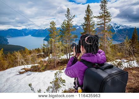 Nature photographer tourist with camera shoots while standing on top of the mountain. Beautiful Nature Norway.