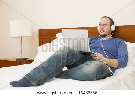 man in bed working with a laptop