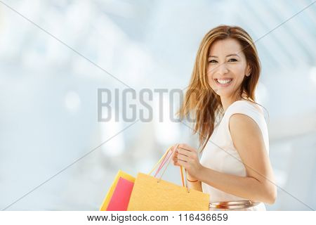 Smiling girls with shopping bags in store