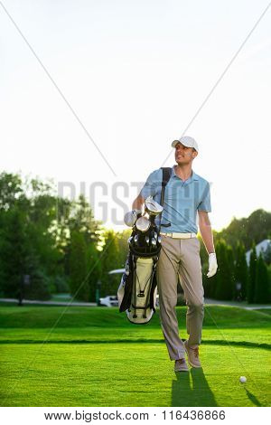 Man with golf clubs on the lawn