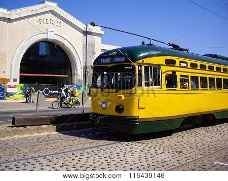 Yellow Tram And Three Wheeled Bike At Pier 15 In San Francisco, California Usa