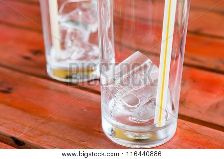 Ice In Glass On Rad Wooden Table