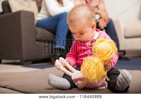 Baby Playing With A Doll Under Supervision