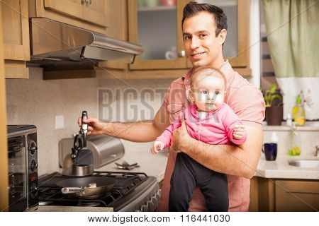 Single Father Cooking Breakfast With A Baby