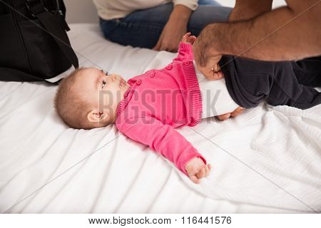Parents Changing Their Baby At Home