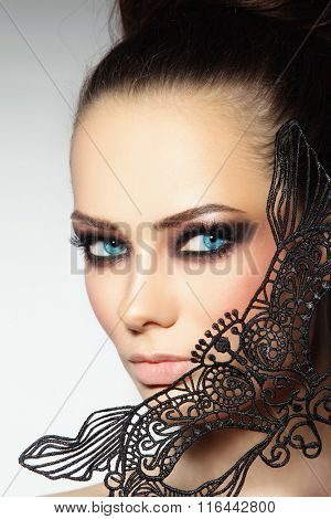 Close-up portrait of young beautiful woman with smoky eyes and lacy black mask