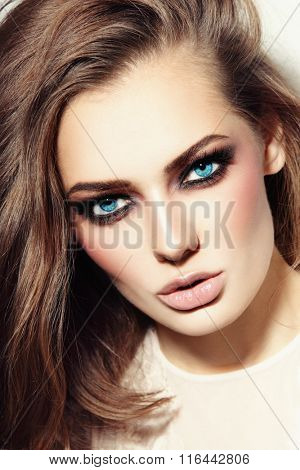 Portrait of young beautiful blue-eyed woman with smoky eyes