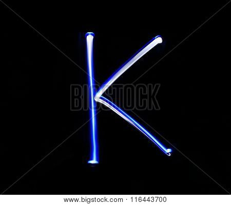 K Kilo Alphabet Hand Writing Blue Light  Over Black Background.