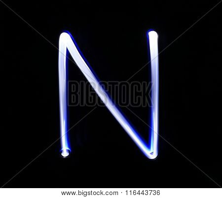 N November Alphabet Hand Writing Blue Light  Over Black Background.