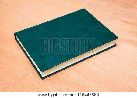 Book With Empty Dark Green Cover On Wooden Table