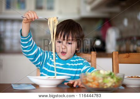 Cute Little Boy, Eating Spaghetti At Home For Lunchtime