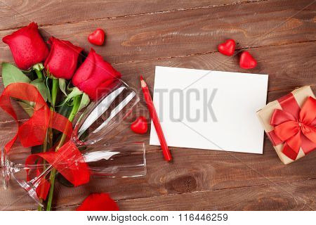 Valentines day greeting card, champagne glasses and red roses on wooden table. Top view with copy space