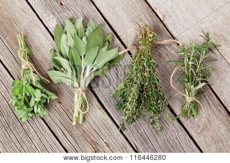 Fresh garden herbs on wooden table. Oregano, thyme, sage, rosemary. Top view
