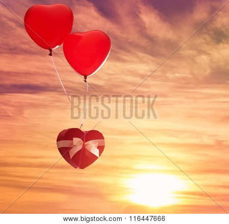 two red balloons in shape of heart and gift box on the background of sunset sky. the concept of love and Valentine's day.