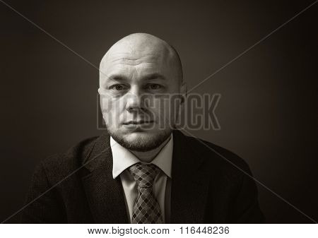 Portrait of an adult man in a business suit on a black background. Unhappy and thoughtful businessman. Sepia