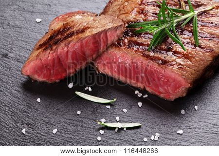 Grilled beef steak with rosemary, salt and pepper on black stone plate