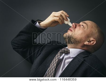Portrait of an adult man in a business suit on a black background. Businessman Suffering From Cold Spraying Nasal Spray In His Nose