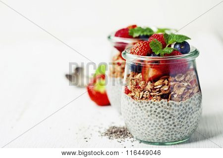 Chia seeds vanilla pudding with berries on wooden background