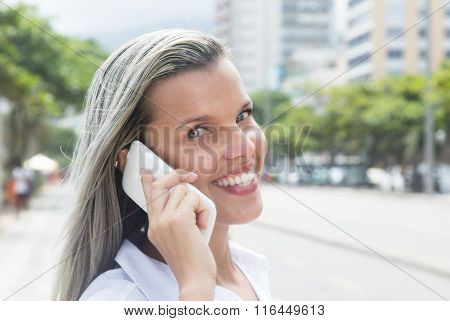Beautiful Woman With Blonde Hair At Phone In The City