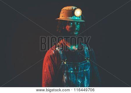 Portrait Of Miner Wearing Helmet Lamp And Overalls