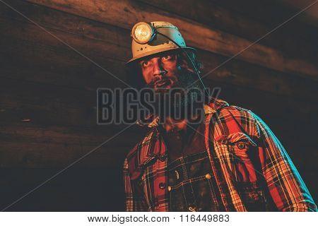 Miner Wearing Helmet Lamp Leaning Against Wall