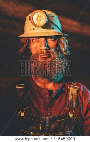 Bearded Miner Wearing Helmet Lamp And Overalls