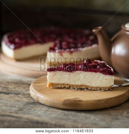 Piece Of Cheesecake With Teapot On Wooden Table