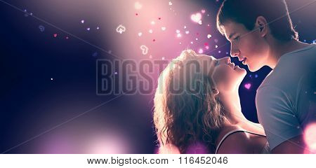 Valentine's Day Young Romantic Couple in love. Beautiful Girl and her boyfriend dancing together, kissing and hugging at night