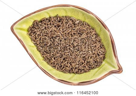 caraway seeds on an isolated leaf shaped ceramic bowl, top view