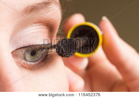 Woman Applying Mascara On Eyelashes.
