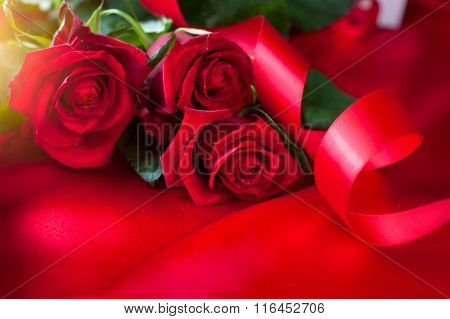 Valentine gift background. Valentine's Day Red Roses bouquet over silk background. Wedding or Valentines Gift. Art design with bunch of beautiful flowers and red satin ribbon closeup