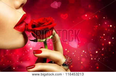 Valentines Day art design. Beautiful Model woman kissing red rose flower. Red Lips, Nails and Rose. Beauty Girl. Makeup and Manicure. Sensual Mouth. Sexy Red Color Lips. St. Valentine's Day design
