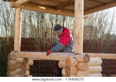 Man Hammers Wooden Rail In The Beam