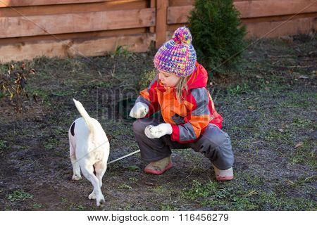 Little Girl Sitting Crouched Beside Dog