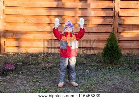 Little Girl Raises Her Hands Up Against Wooden Fence