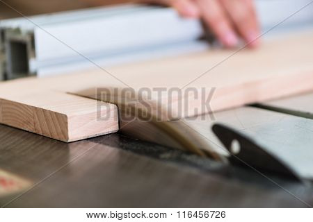 Carpenter cutting wooden board with circular saw
