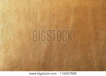 Golden leather texture with uneven surface