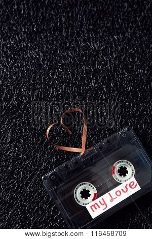 Retro audio cassette with tape in shape of heart on black textured background