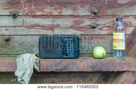 Still Life On A Wooden Shelf: Rag, Not A Ripe Tomato, Radio, Bottle Of Kerosene