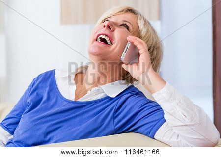 Senior woman phone at home sitting on couch